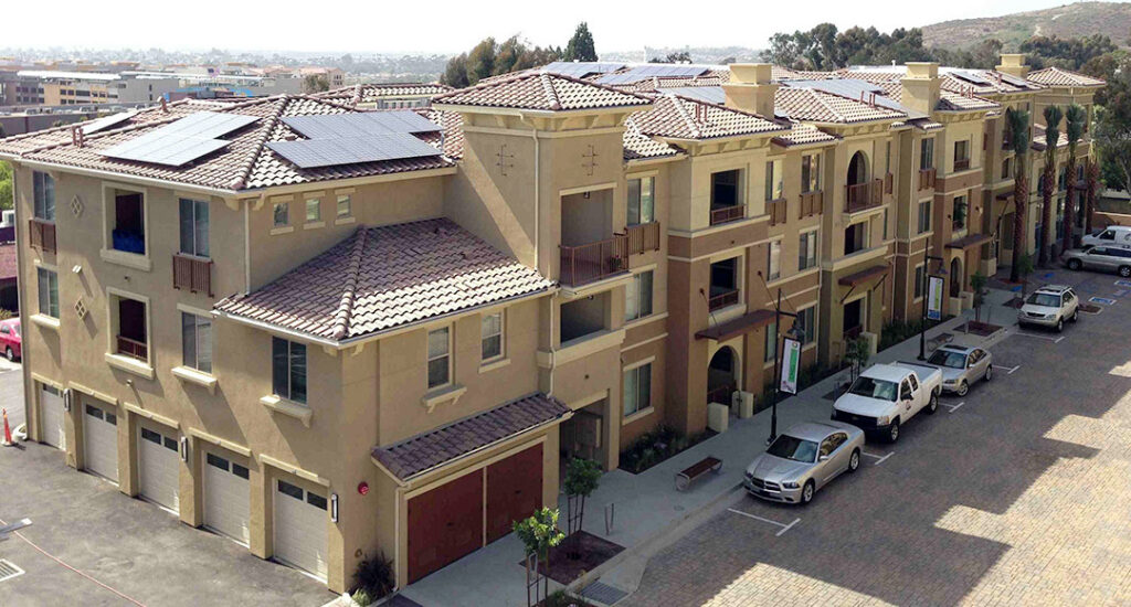 Multi family apartment with many solar panel arrays on the roofs