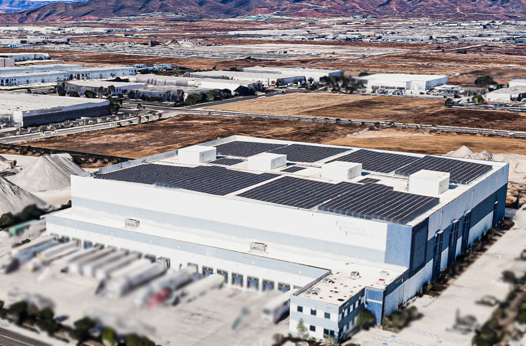 Aerial view of cold storage building with large commercial solar system on the roof.